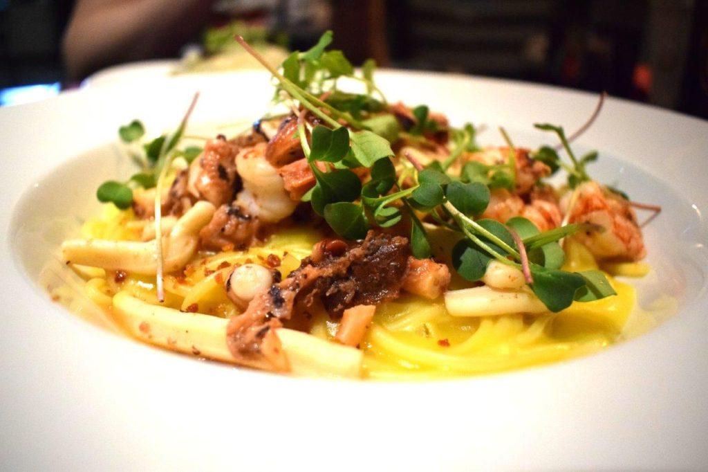 Spaghetti ao Creme de Mandioquinha com Refogado do Mar, Farofinha de Bacon e Brotos Variados.